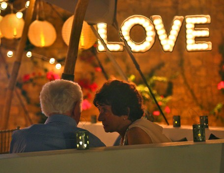 elderly couple by love sign - Elixir Shore Club