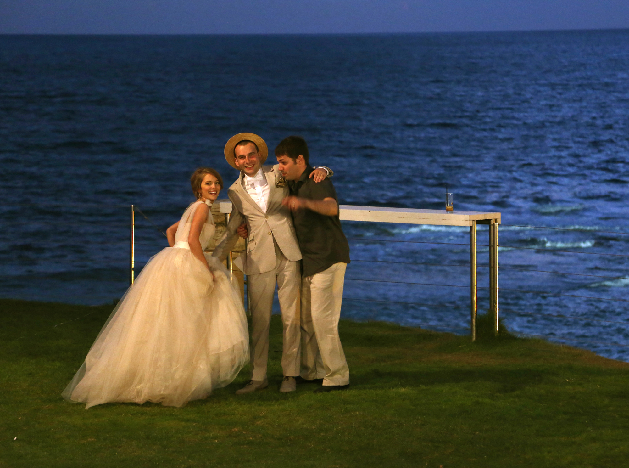 wedding couple with friend by sea