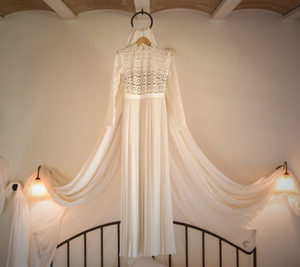 wedding dress hung above bed