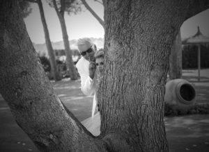 wedded couple bbehind tree