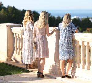 three girls look towards sea
