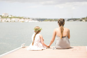 woman and girl by water holding hands