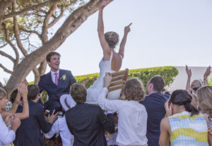 bride and groom on chairs aloft