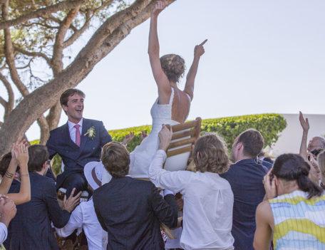 bride and groom on chairs aloft - Hotel Sant Joan de Binissaida