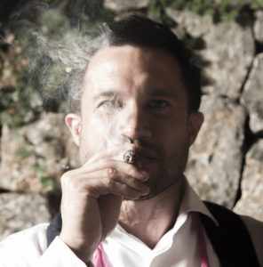 man with cigar poses for photograph
