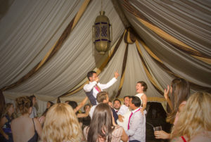 couple held aloft at wedding party
