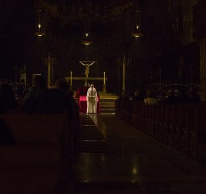 Catholic priest stands at alter