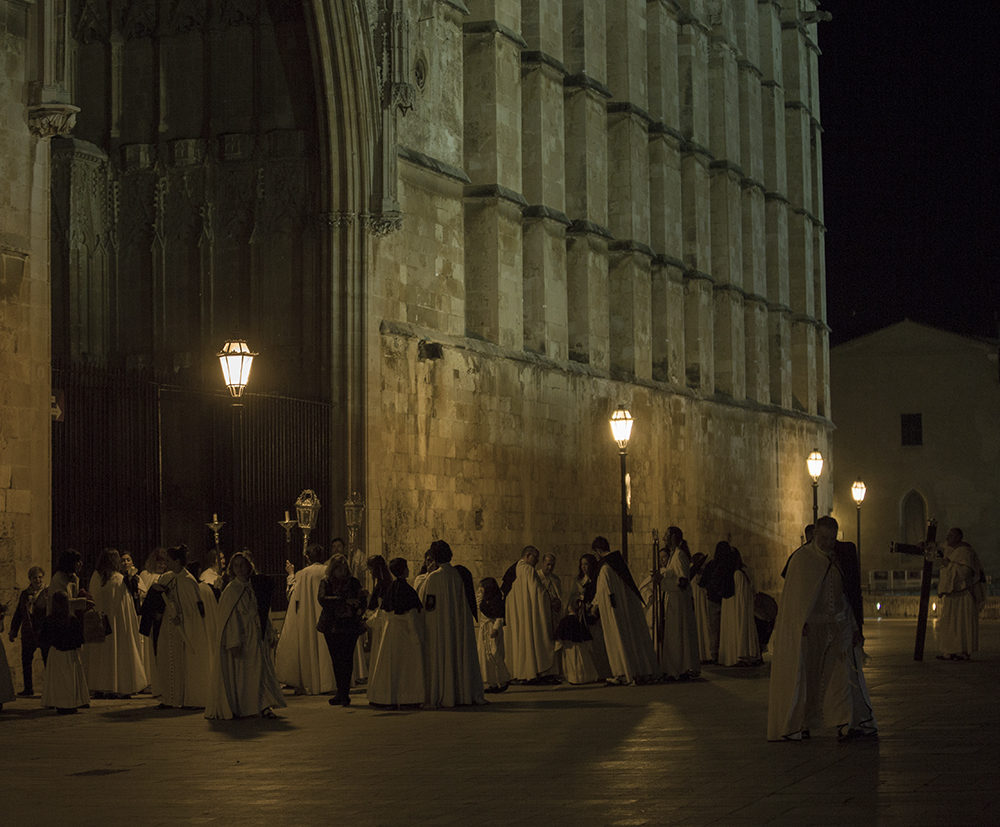 Religious people in costume stand outside Palma Cathedral