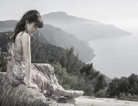 woman on wall overlooking mountains and sea - Portrait Photography