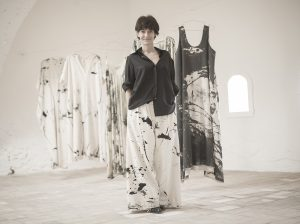 Woman stands in front of hung clothes